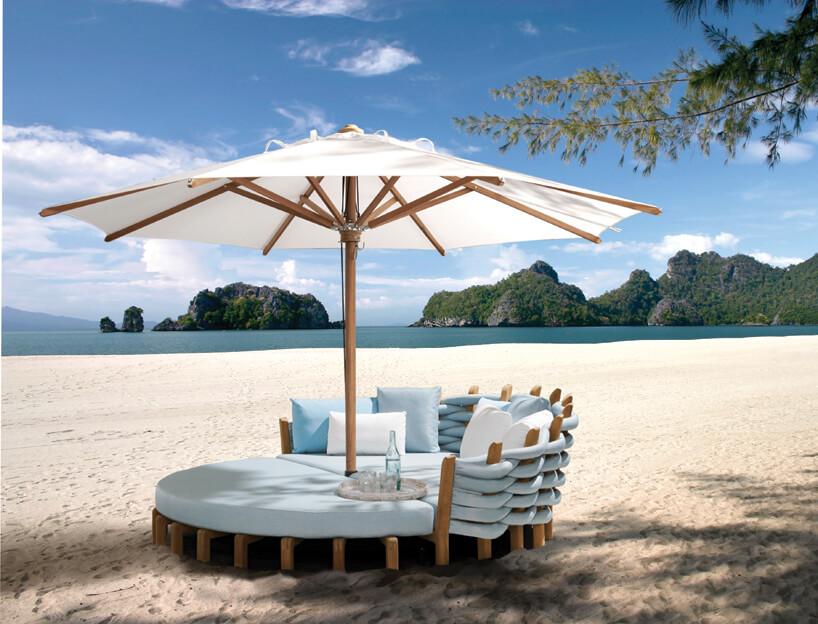 ekskluzywne drewniana leżanka Lotus iShady od Royal Botania zbeżowym drewnianym parasolem na nadmorskiej plaży