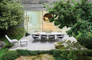ekskluzywne meble ogrodowe Exes i Folia od Royal Botania biały owalny stół na czarnych metalowych nogach z czarnymi krzesłami z cienkich prętów na małym tarasie