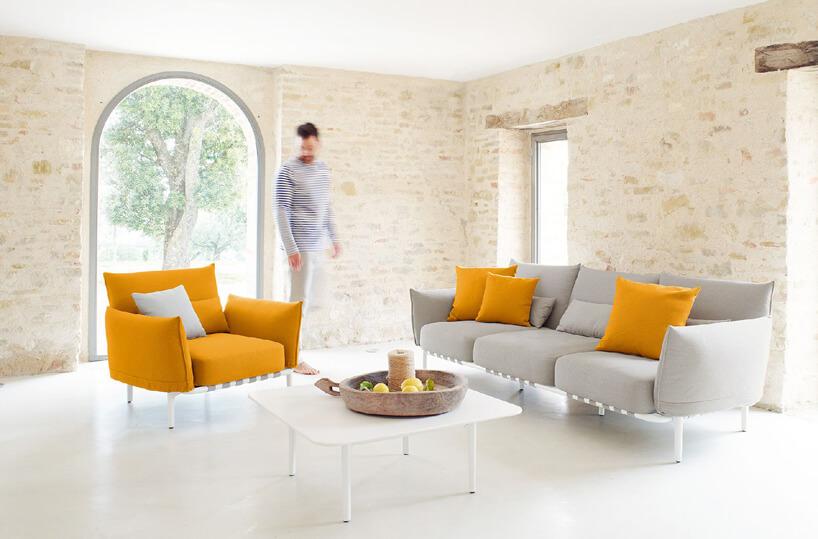 jasny zestaw ogrodowy sofa ifotel wjasnym wnętrzu obok żółtego fotela
