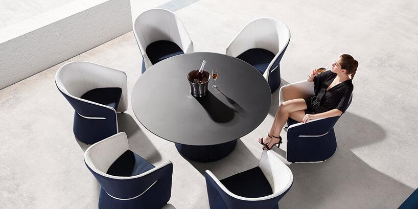 elegancka kobieta siedząca na ekskluzywnym biało-czarnym ogrodowym fotelu przy czarny stole ogrodowym