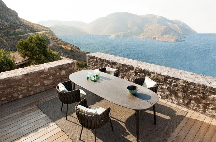 duży stół zczterema krzesłami na tarasie na tle zatoki