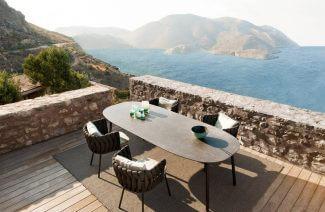 duży stół z czterema krzesłami na tarasie na tle zatoki