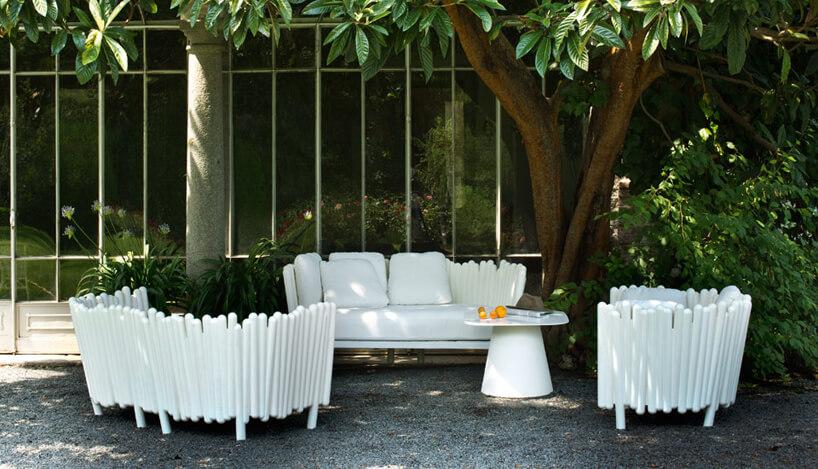 białe plastikowe siedziska ogrodowe wcieniu drzewa