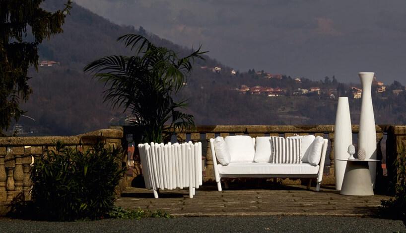 białe plastikowe siedziska ogrodowe na tarasie na tle zatoki