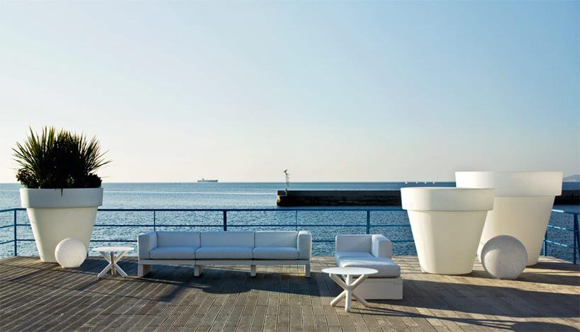 białe meble ogrodowe na tarasie nad brzegiem morza