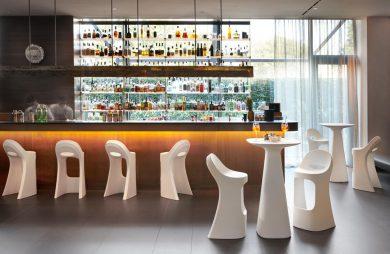 bar z białymi wysokimi plastikowymi stołkami i stolikiem