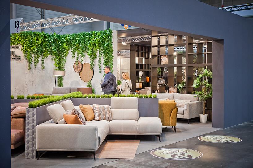 jedno zwyjątkowych stoisk zbeżową narożną sofą na stoisku podczas targów Meble Polska 2020
