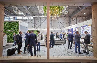 odwiedzający podczas targów Meble Polska 2020 za ścianą z drewnianych grubych desek z rozciągniętymi czarnymi sznurkami wewnątrz