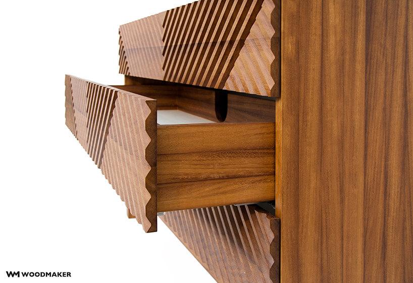 brązowa drewniana komoda ze zdobionym frontem zotwartą szufladą