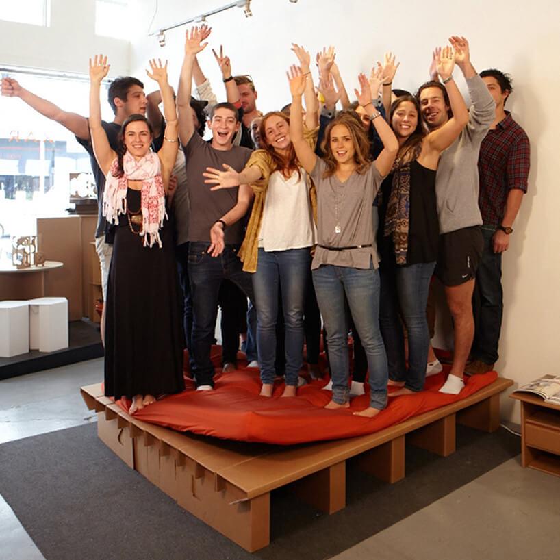 grupa ludzi stojących na tekturowych meblach