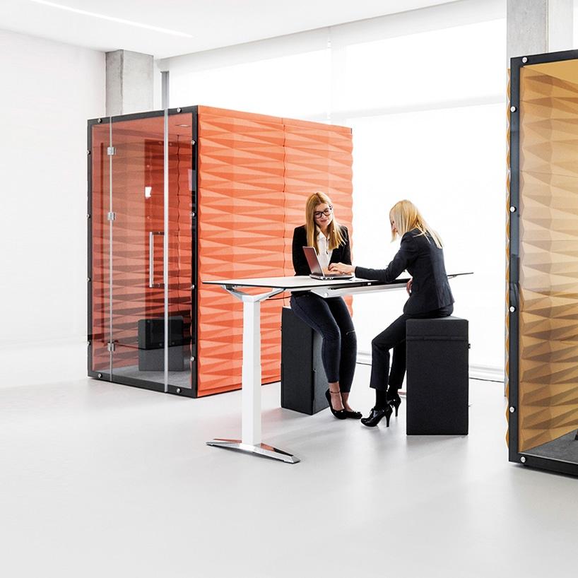 dwie eleganckie kobiety przy białym biurku zczarnymi wysokimi pufami