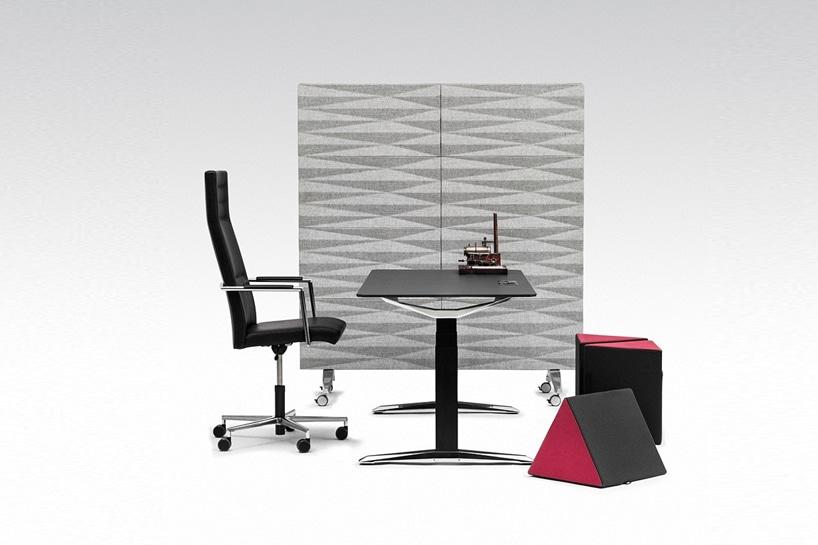 trójkątne czarno czerwone pufy od VANK przy czarny nowoczesnym eleganckim biurku