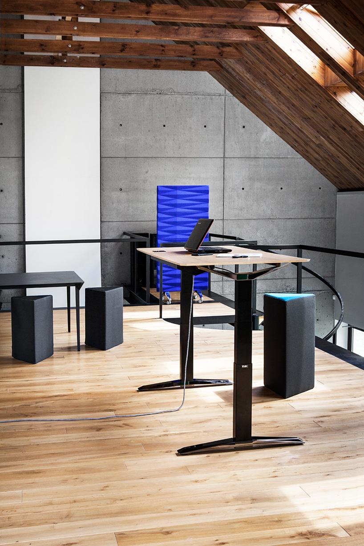 wysokie czarne biurko zregulowaną wysokością zdrewnianym blatem iczarnymi trójkątnym pufami od VANK