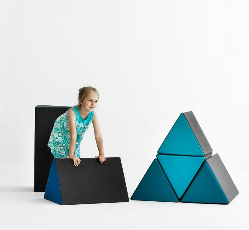 dziecko pośród czarno niebieskich trójkątnych puff