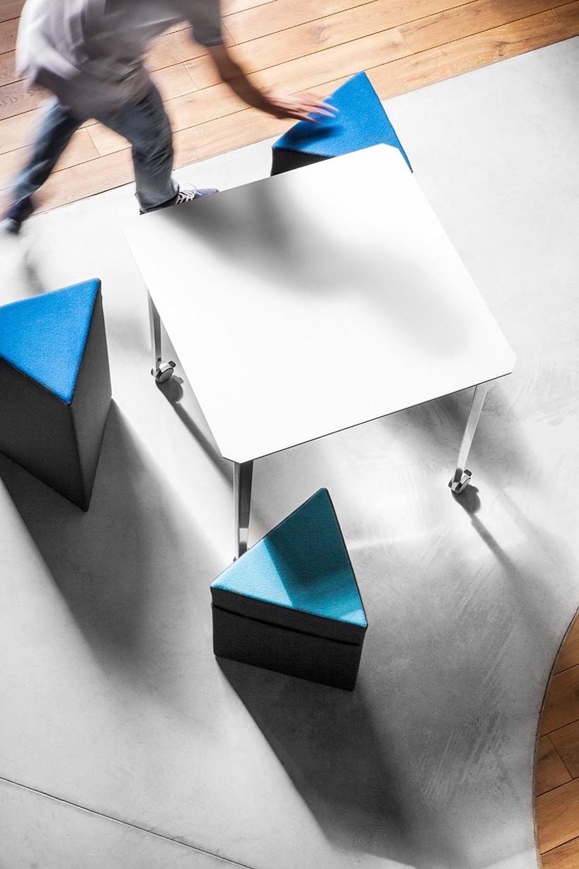 trzy czarno niebieskie trójkątne pufy przy białym stoliku na kółkach