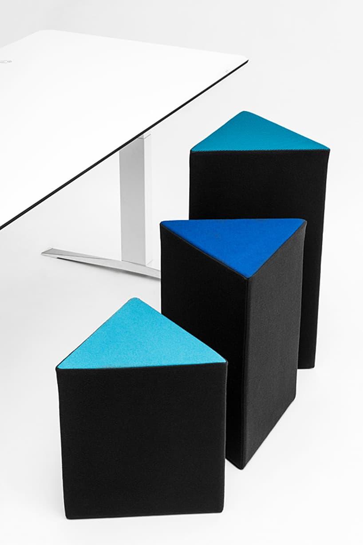 trzy czarno niebieskie pufy od VANK oróżnej wysokości przy białym biurku