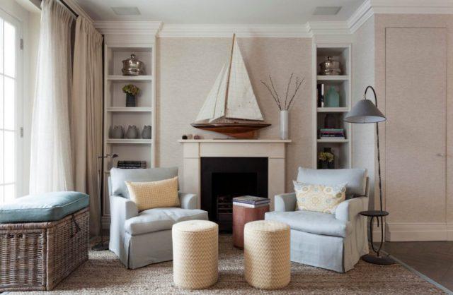 salon z dwoma fotlami i z żaglówką na ścianie