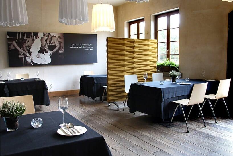 wykfintna restautracja zczarnymi obrusami na stołach ztalerzami wpomieszczeniu zwysokimi oknami
