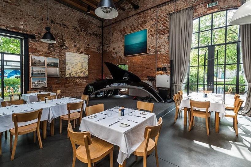 wnętrze restauracji zdrewnianeymi krzesłami oraz białymi obrusami na stołach obok starych ceglanych ścian zobrazami