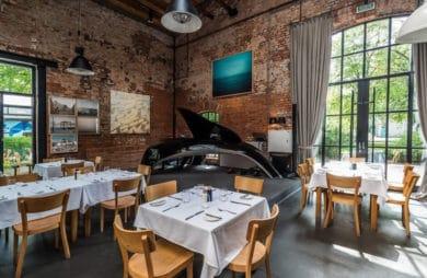 wnętrze restauracji z drewnianeymi krzesłami oraz białymi obrusami na stołach obok starych ceglanych ścian z obrazami
