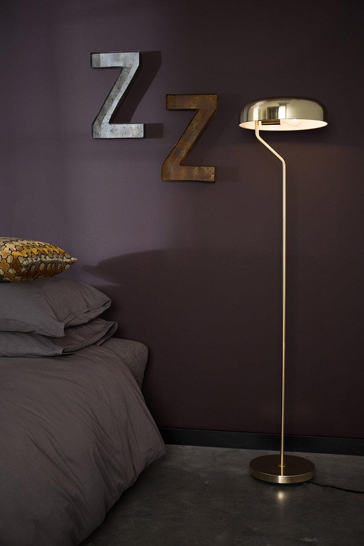 wysoka metalowa lampa na tle fioletowej ściany