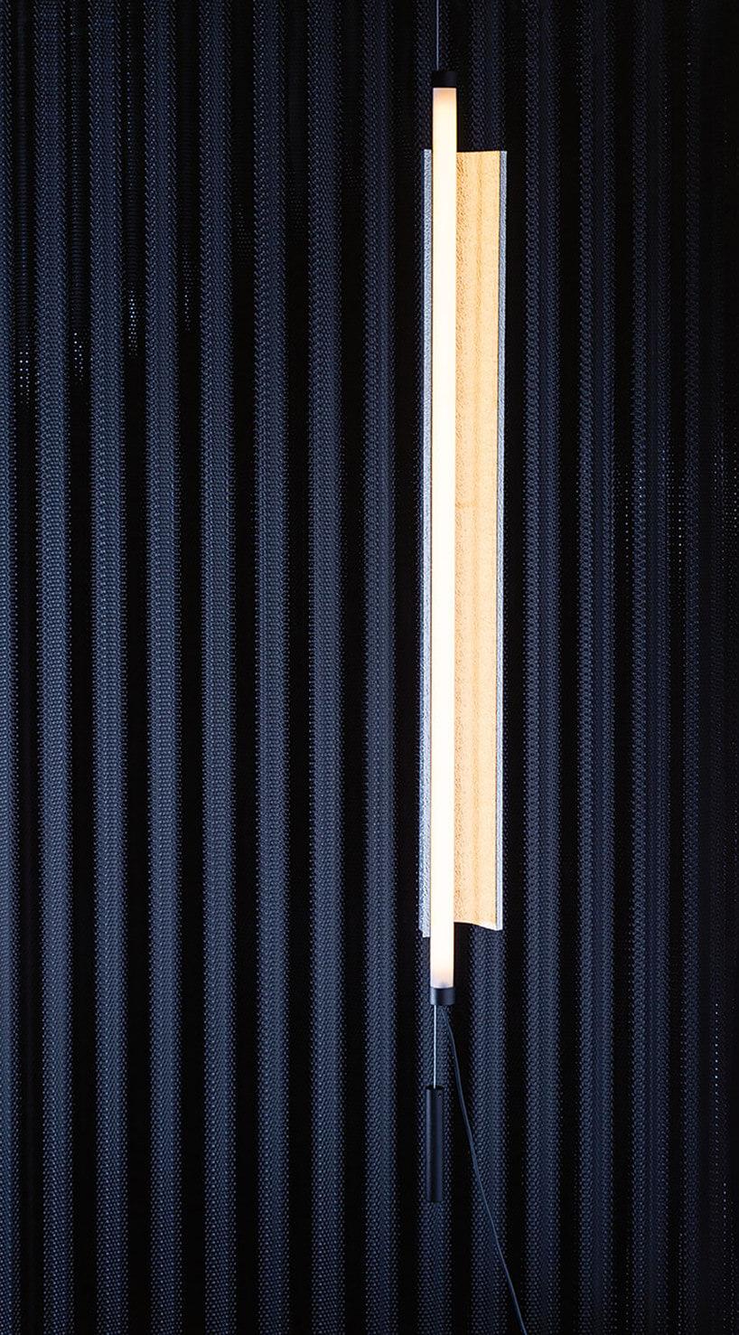 podłużna lampa na tle niebieskiej perforowanej ścinie