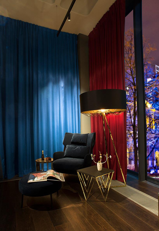 duża lampa stojąca iefektowny stolik obok czarnego fotela