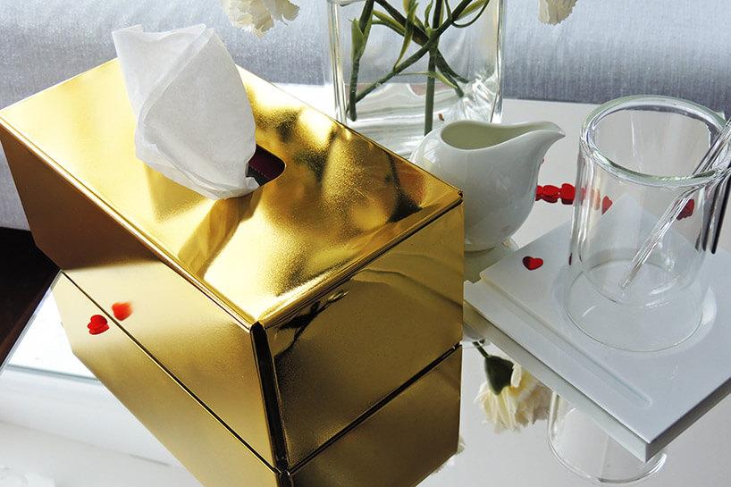 złoty pojemnik na chusteczki na lustrzanym stoliku