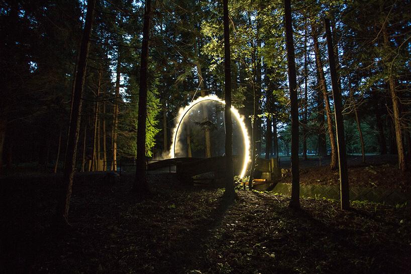 podświetlona sztuczna mgła wmrocznym lesie