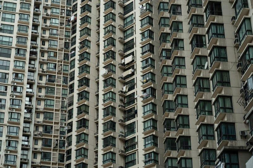 schodkowy szary front wieżowca mieszkalnego wcentrum miasta