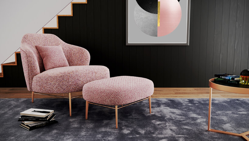 różowy zestaw fotel ipodnóżek na niebieskim dywanie ina tle czarnej ściany
