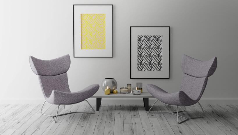 dwa różowe krzesła zgłębokim siedziskiem na tle szarej ściany zdwoma obrazami