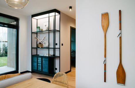 wnętrze mieszkania w Gdyni Jelitkowo projektu pracowni Plan A jadalnia z dwoma wiosłami na szarej ścianie i czarny elegancki regał