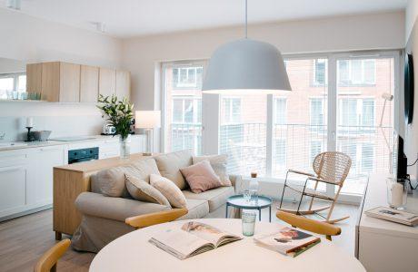 wnętrze mieszkania w Gdyni Stare Miasto projektu pracowni Plan A jasna kawalerka z biało drewnianym aneksem kuchennymi i beżową sofą na tle dużego białego okna