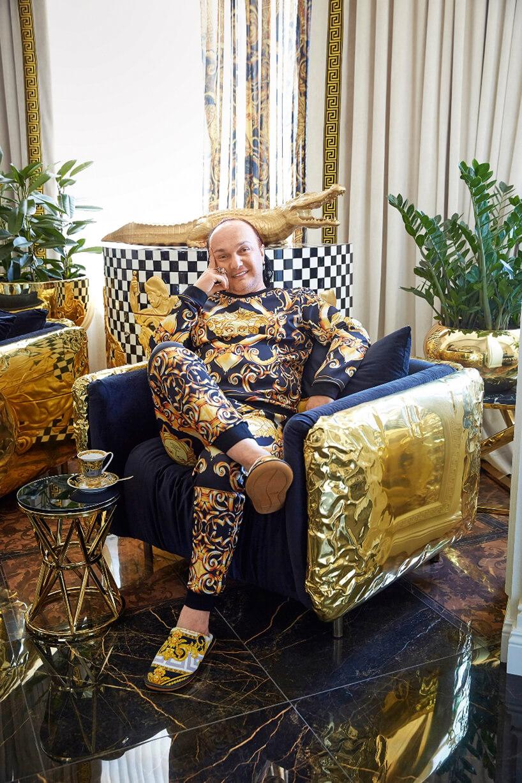 mężczyzna wzdobionej piżamie siedzący wniebieskim fotelu ze złotymi zdobieniami