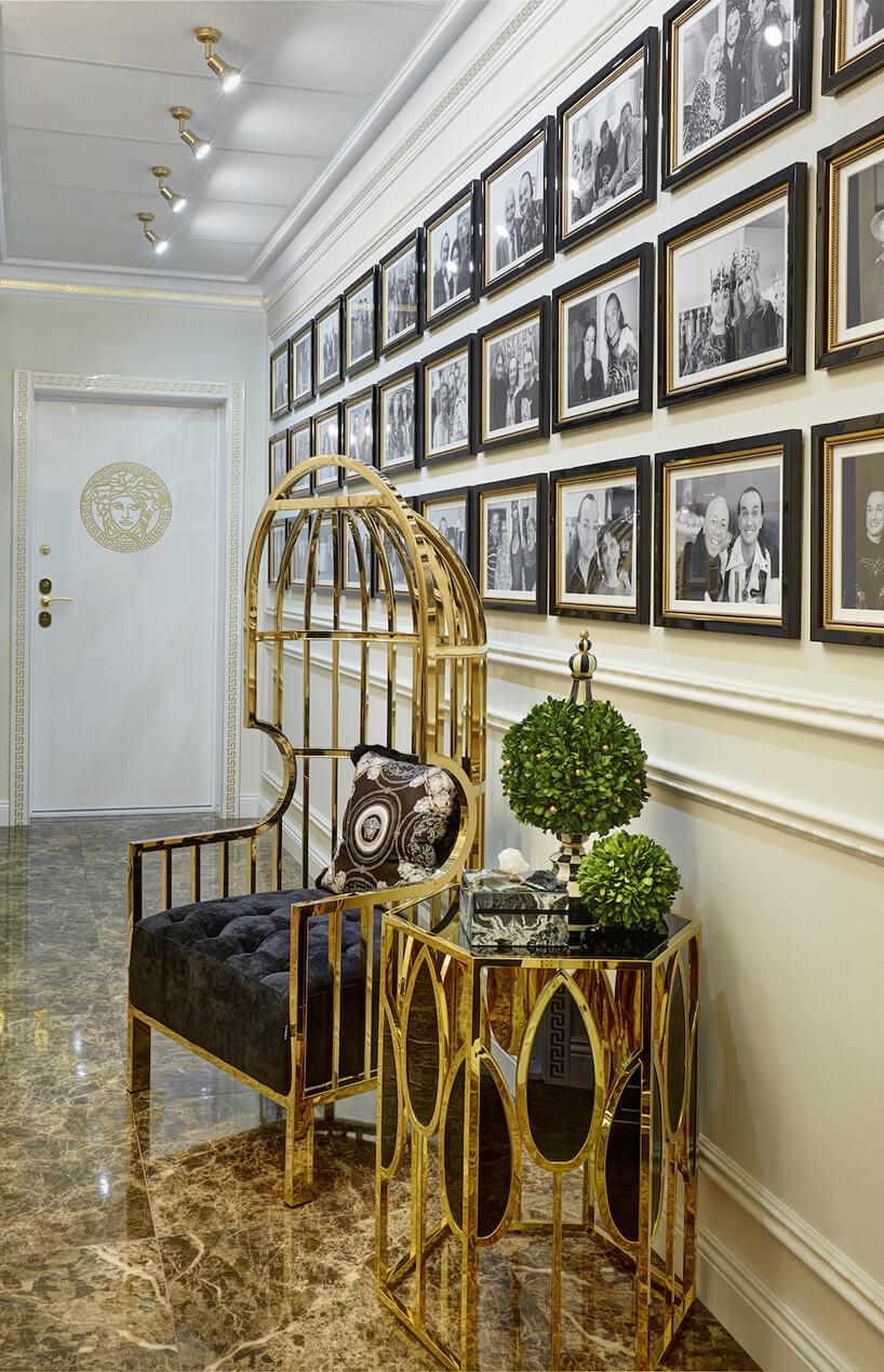 hol ze stolikiem ifotelem ze złotych prętów na tle ściany ze zdjęciami