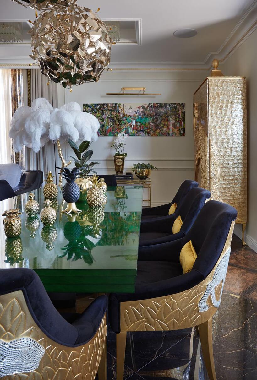 zielony stół wjadalni zgranatowymi krzesłąmi ze złotymi wykończeniami