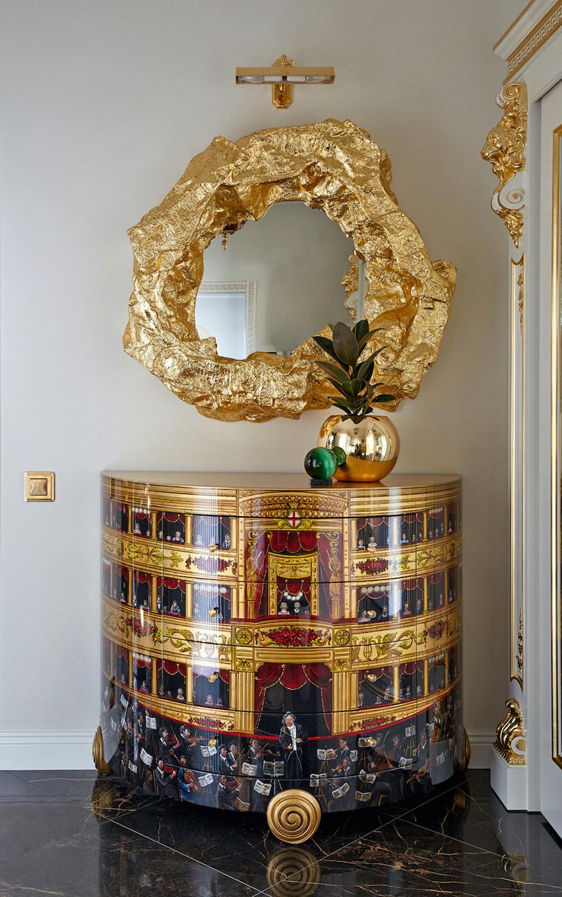 lustro zgrubą złotą ramą nad stolikiem ze złotym malowaniem