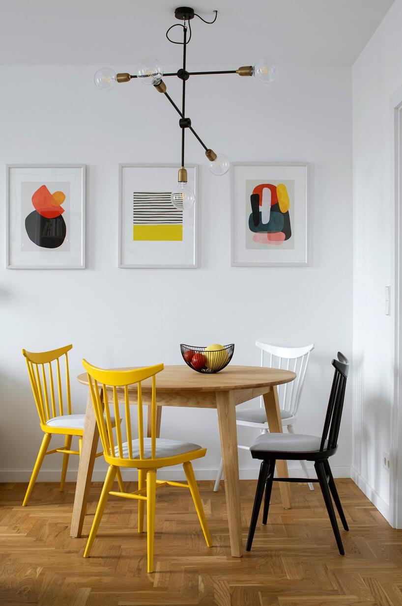 niewielki okrągły stół zczterema różnokolorowymi krzesłami