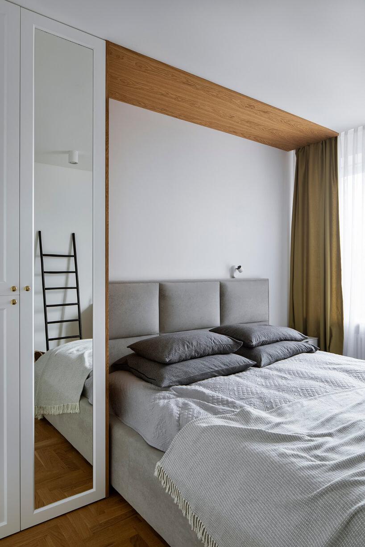 duże szare łóżko obok białej szafy zlustrem wbiałej sypialni