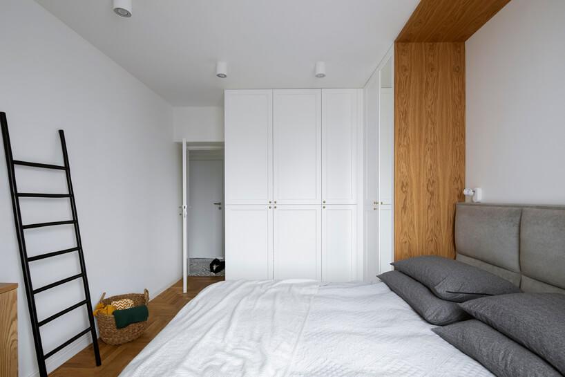 duże łóżko wbiałej sypialni zdużą szafą na całej ścianie