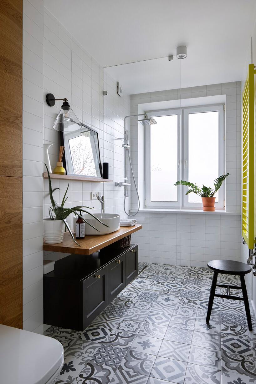 biała łazienka zdrewnianymi akcentami czarnymi szafkami izielonym grzejnikiem