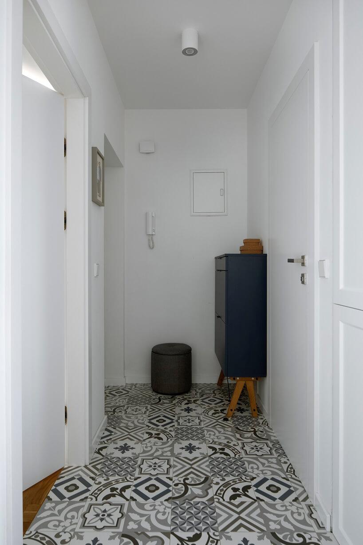 biały przedpokój zwzorzystą podłoga zkafelek małą pufą iciemno niebieską szafką