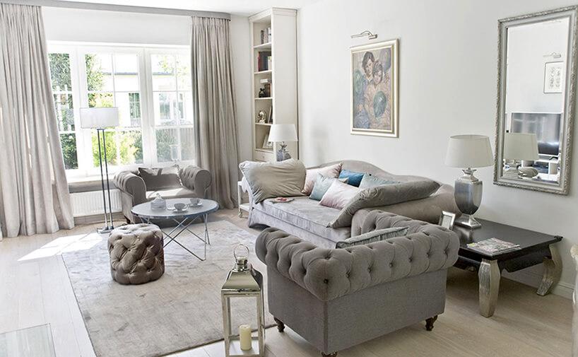 eleganckie wnętrze projektu MIśkiewicz Design salon szara sofa zdwoma szarymi fotelami ibłyszcząca pufą