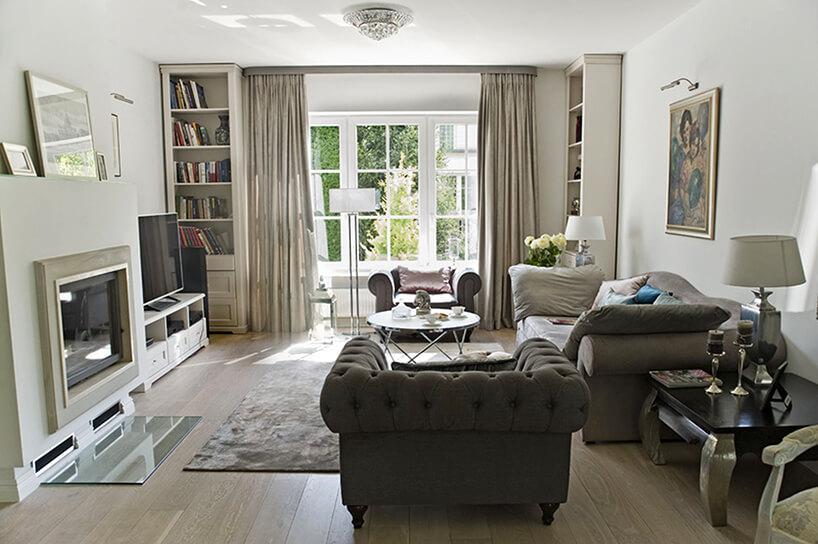 eleganckie wnętrze projektu Miśkiewicz Design jasny salon zzabudowanym kominkiem na tle wysokiego białego okna