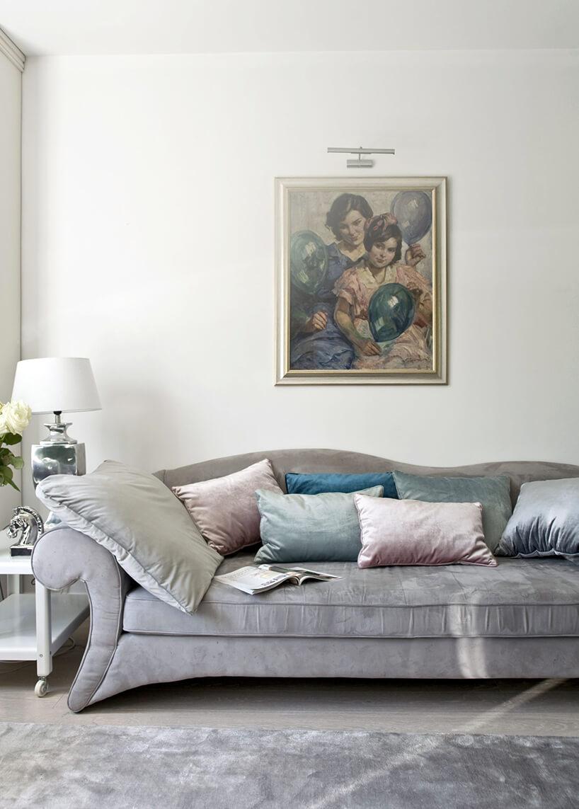 eleganckie wnętrze projektu Miśkiewicz Design elegancka srebrna sofa zbłyszczącymi poduszkami dekoracyjnymi pod obrazem na jasnej ścianie
