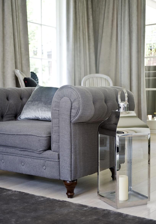 eleganckie wnętrze projektu Miśkiewicz Design szary fotel zniskim oparciem obok zabudowanego świecznika wkształcie lampionu