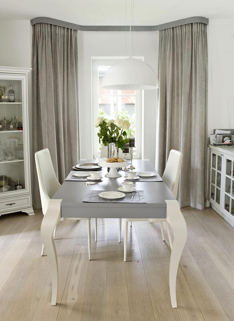 eleganckie wnętrze projektu Miśkiewicz Design drewniany malowany stół zszarym blatem ibiałymi nogami zbiałymi krzesłami