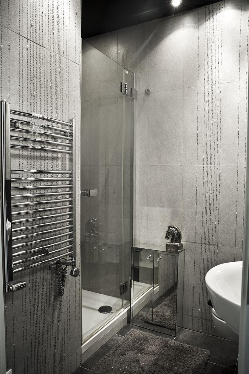 eleganckie wnętrze projektu Miśkiewicz Design szara łązienka zmałą błyszcząca szafką ibłyszczącym grzejnikiem szara łazienka znatryskiem ze szklanymi drzwiami