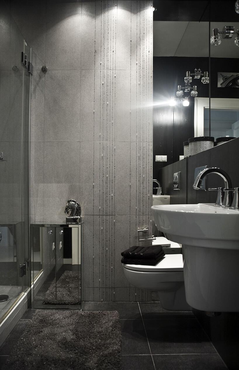 eleganckie wnętrze projektu Miśkiewicz Design szara łazienka zbłyszczącą chromowaną małą szafką